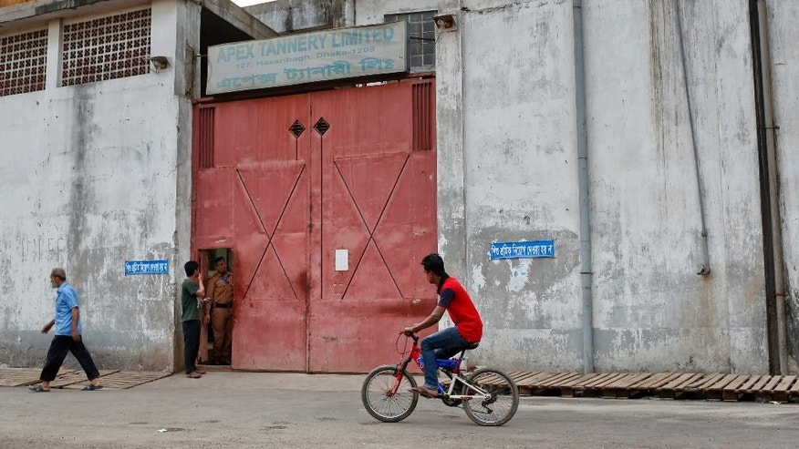 In this Thursday, March 2, 2017 photo, a Bangladeshi man rides past a bicycle in front of the main entrance of the Apex tannery at the highly polluted Hazaribagh tannery area in Dhaka, Bangladesh. Hazardous, heavily polluting tanneries with workers as young as 14 supplied leather to companies that make shoes and handbags for Western brands, a nonprofit group that investigates supply chains says. (AP Photo/A.M. Ahad)