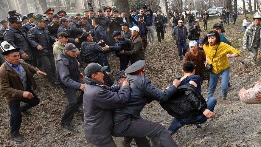 Kyrgyz police officers detain a demonstrator during a protest in Bishkek, Kyrgyzstan, Saturday, March 25, 2017. Supporters of a jailed former parliament member tried to break through a police cordon outside the national security agency's headquarters in Kyrgyzstan's capital, but police turned them back with flash grenades and arrested dozens. About 250 people had gathered in Bishkek to call for the release of Sadyr Jarapov, who was arrested when trying to enter the country earlier in the day. (AP Photo/Vladimir Voronin)