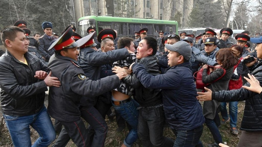 Kyrgyz police officers detain demonstrators during a protest in Bishkek, Kyrgyzstan, Saturday, March 25, 2017. Supporters of a jailed former parliament member tried to break through a police cordon outside the national security agency's headquarters in Kyrgyzstan's capital, but police turned them back with flash grenades and arrested dozens. About 250 people had gathered in Bishkek to call for the release of Sadyr Jarapov, who was arrested when trying to enter the country earlier in the day. (AP Photo/Vladimir Voronin)
