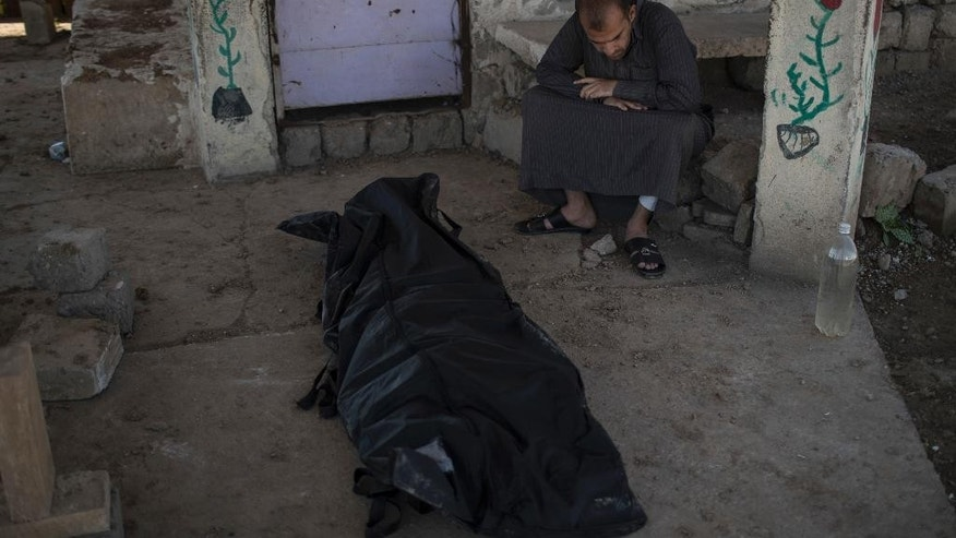 A man sits next to the body of Khadeer Hassan, who was killed during fighting between Iraqi security forces and Islamic State on the western side of Mosul, Iraq, Saturday, March 25, 2017. (AP Photo/Felipe Dana)