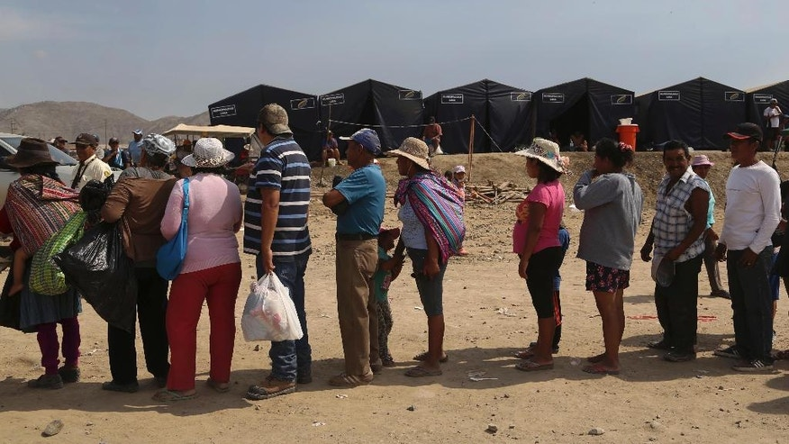 In this March 24, 2017 photo, flood survivors stand in a food line at a refugee camp in Carapongo, Peru. Peru is expected to spend at least $3.75 million in repairing bridges and roads, according to the Central Bank, but the economic toll is still accumulating. Another two weeks of rain are forecast and the state meteorological agency expects the ocean warming causing the storms to continue through April. (AP Photo/Martin Mejia)