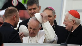 Pope Francis changes his skull cap as he arrives at Milan's Linate airport, northern Italy, for a one-day pastoral visit to Monza and Milan, Italy's second-largest city, Saturday, March 25, 2017. On Friday Francis welcomed 27 EU leaders to the Vatican on the eve of a summit to mark the 60th anniversary of the Treaty of Rome, the founding charter of the bloc. At right the Archbishop of Milan, Cardinal Angelo Scola looks on. (AP Photo/Luca Bruno)