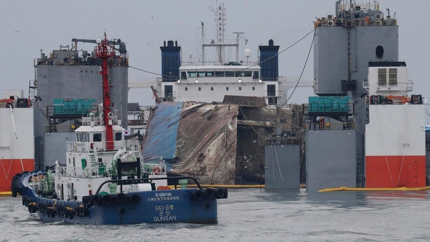 The sunken ferry Sewol is loaded onto a semi-submersible transport vessel during the salvage operation in waters off Jindo, South Korea, Saturday, March 25, 2017. Days after South Korean President Park Geun-hye was removed from office, the ferry was lifted slowly from the waters where it sank three years earlier - a disaster that killed more than 300 people, mostly schoolchildren, and ignited public fury against Park and became a nationally polarizing issue. (Lee Jin-wook/Yonhap via AP)