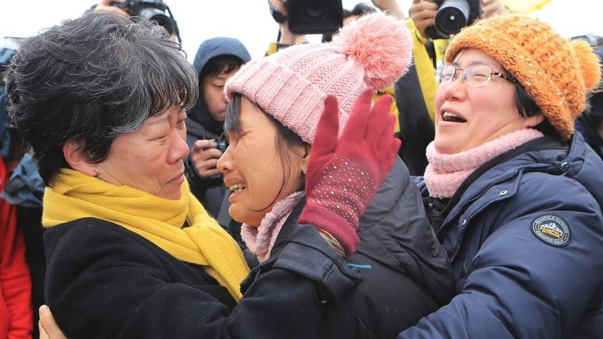Relatives of missing passengers of the sunken ferry Sewol react as they watch the salvage operation under way in the waters off Jindo, South Korea, Saturday, March 25, 2017. Days after South Korean President Park Geun-hye was removed from office, the ferry was lifted slowly from the waters where it sank three years earlier - a disaster that killed more than 300 people, mostly schoolchildren, and ignited public fury against Park and became a nationally polarizing issue. (Lee Jin-wook/Yonhap via AP)
