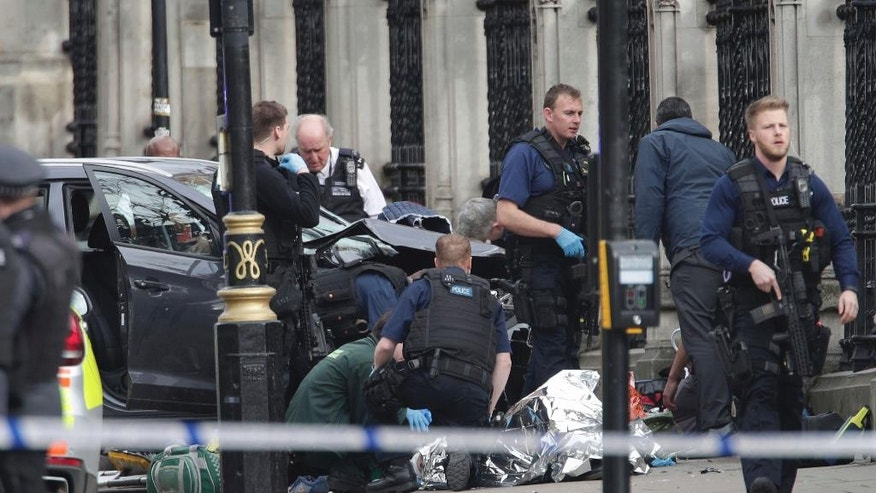 FILE - In this March 22, 2017 file photo, emergency personnel tend to an injured person outside Britain's Parliament after an attack by a British-born man. The attack was claimed by the Islamic State group, which is encouraging its followers to use vehicles to achieve bloodshed.  (Yui Mok/PA via AP, File)