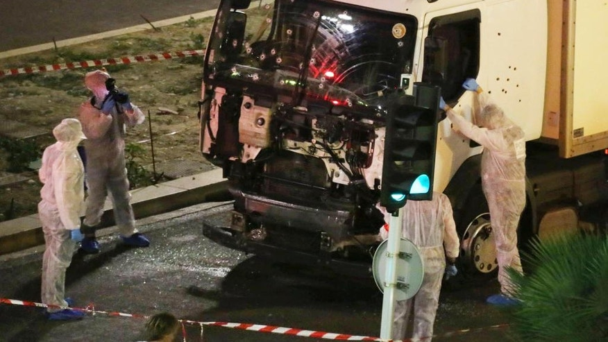FILE - In this July 14, 2016 file photo, authorities investigate a truck after it plowed through Bastille Day revelers in the French resort city of Nice, France, killing 86 people. In Britain, a man drove a car into pedestrians in London on March 22, 2017, in an attack claimed by the Islamic State group. The extremist group is encouraging its followers to use vehicles to achieve bloodshed. (Sasha Goldsmith via AP, File)