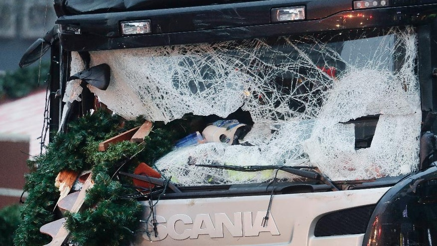 FILE - In this Dec. 20, 2016 file photo, Christmas decoration are stuck in the smashed window of the cabin of a truck which ran into a crowded Christmas market. The death toll from the attack was 12. In Britain, a man drove a car into pedestrians in London on March 22, 2017, in an attack claimed by the Islamic State group. The extremist group is encouraging its followers to use vehicles to achieve bloodshed. (AP Photo/Markus Schreiber, File)