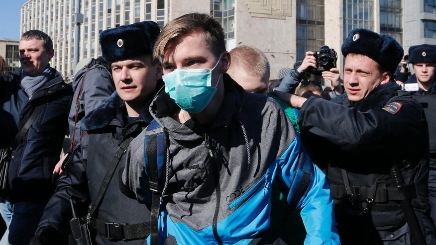 "Police detain a protester in downtown Moscow, Russia, Sunday, March 26, 2017. Russia's leading opposition figure Alexei Navalny and his supporters aim to hold anti-corruption demonstrations throughout Russia. But authorities are denying permission and police have warned they won't be responsible for ""negative consequences"" or unsanctioned gatherings. (AP Photo/Alexander Zemlianichenko)"
