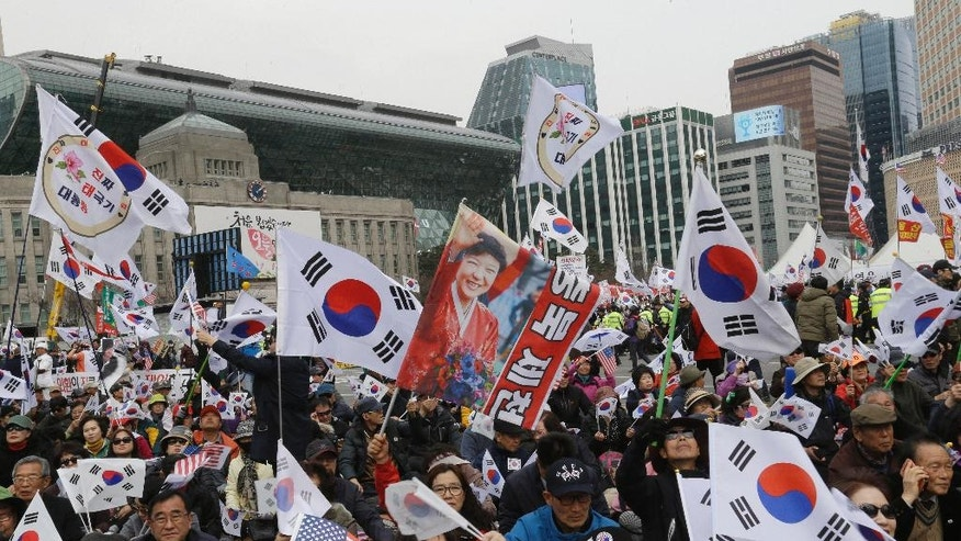 FILE - In this March, 25, 2017 file photo, supporters of ousted South Korean President Park Geun-hye stage a rally opposing her impeachment in Seoul, South Korea. Media reports say that South Korean prosecutors have decided to ask a court issue a warrant to arrest former President Park Geun-hye on corruption allegations. Yonhap news agency reported Monday, March 27 2017,  that prosecutors reached the decision after they grilled Park last week over suspicions she colluded with a jailed confidante to extort from companies and allowed the friend to secretly interfere with state affairs. (AP Photo/Ahn Young-joon, File)