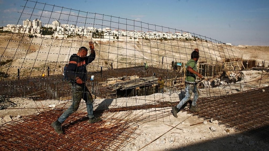 File -- In this Jan. 22, 2017 file photo, workers carry material at a construction site in the West Bank settlement of Maaleh Adumim. Yaakov Katz, a prominent West Bank settler, said Sunday, March 26, 2017, that the number of Israelis living in the West Bank has soared by nearly one quarter over the past five years to over 420,000 people. Katz says the rapid growth means the internationally backed idea of a two-state solution between Israel and the Palestinians is now impossible. (AP Photo/Mahmoud Illean, File)