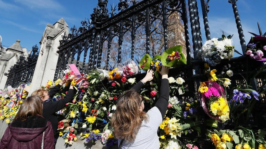 People place flowers outside Britain's parliament in London, Saturday March 25, 2017, for the victims of the Westminster attack on Wednesday. Khalid Masood killed four people and left more than two dozen hospitalized, including some with what have been described as catastrophic injuries. The Islamic State group claimed responsibility for the attack.(AP Photo/Kirsty Wigglesworth)