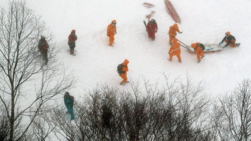Firefighters make rescue operation at a ski resort following an avalanche in Nasu, Tochigi prefecture, Monday,  March 27, 2017. Several high school students are feared dead after being caught in an avalanche Monday during a mountain climbing outing at a ski resort. (Kyodo News via AP)