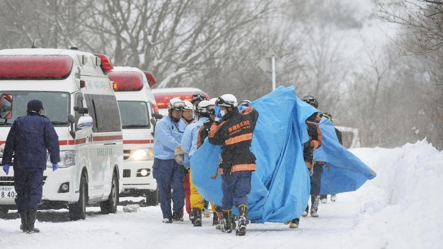 Rescuers carry the people who got injured in an avalanche at a ski resort in Nasu, Tochigi prefecture, Monday,  March 27, 2017.  Eight Japanese high school students are feared dead after being caught in an avalanche Monday during a mountain climbing outing at a ski resort, authorities and media said.  (Yoshitaka Sugawara/Kyodo News via AP)