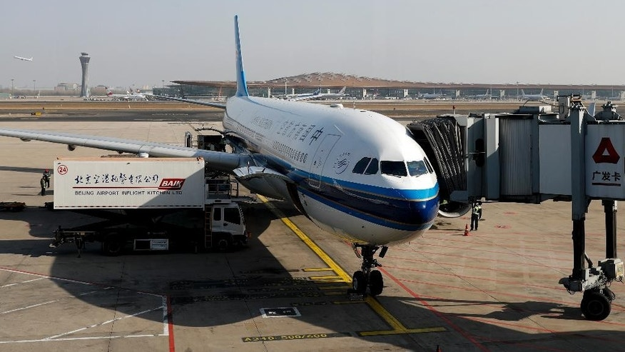 In this Saturday, Nov. 19, 2016 photo, workers loading in-flight catering into a passenger airplane, owned by China Southern Airlines, parked on the tarmac at the Beijing Capital International Airport. American Airlines has agreed to pay $200 million for a stake in China Southern Airlines, the biggest of China's three major state-owned carriers, in a bid for a bigger share of the country's growing travel market. (AP Photo/Andy Wong)