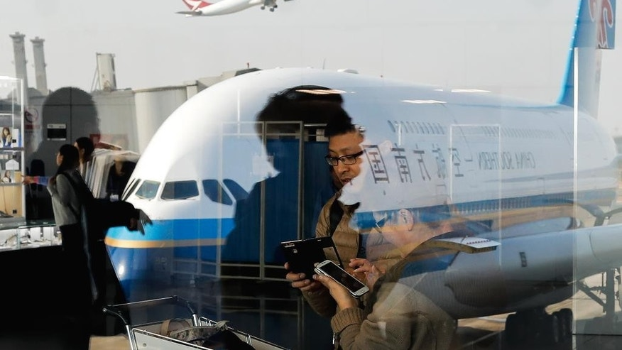 FILE - In this Saturday, Nov. 19, 2016 file photo, passengers walk past a couple browsing their smartphones near an Airbus A380 passenger airplane, owned by China Southern Airlines, parked on the tarmac at the Beijing Capital International Airport. American Airlines has agreed to pay $200 million for a stake in China Southern Airlines, the biggest of China's three major state-owned carriers, in a bid for a bigger share of the country's growing travel market. (AP Photo/Andy Wong, File)