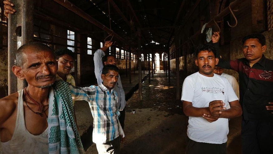 In this Sunday, March 26, 2017 photo, workers stand at a slaughter house where they used to work after the same was shutdown by authorities in Allahabad, India.  India's most populous state is running out of meat. After the Hindu right-wing Bharatiya Janata Party came to power in Uttar Pradesh this month on the back of a resounding electoral victory and named a Hindu priest-cum-politician as the state's chief minister, the government began cracking down on illegal slaughterhouses and meat shops. (AP Photo/Rajesh Kumar Singh)