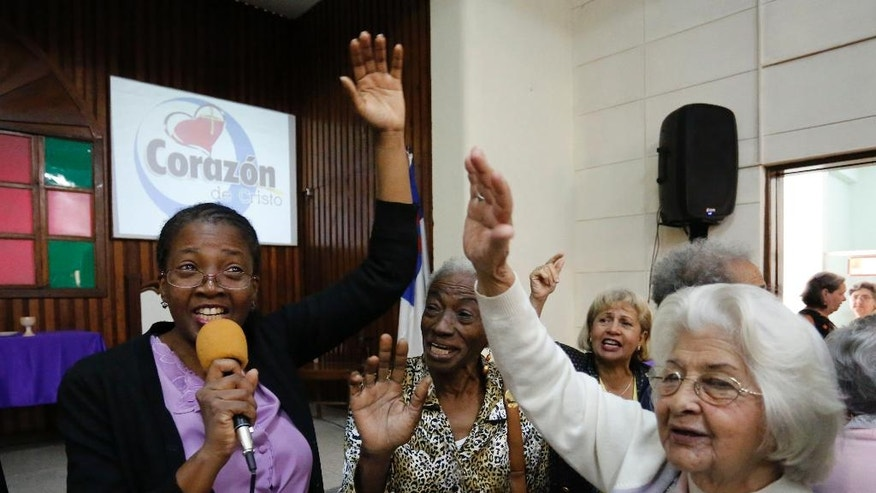 In this March 19, 2017 photo, people sing as they attend Sunday worship at the William Carey Baptist Church in Havana, Cuba. Like the Roman Catholic church, the island's dominant denomination, evangelical churches have begun providing social services once monopolized by the Communist government. (AP Photo/Desmond Boylan)