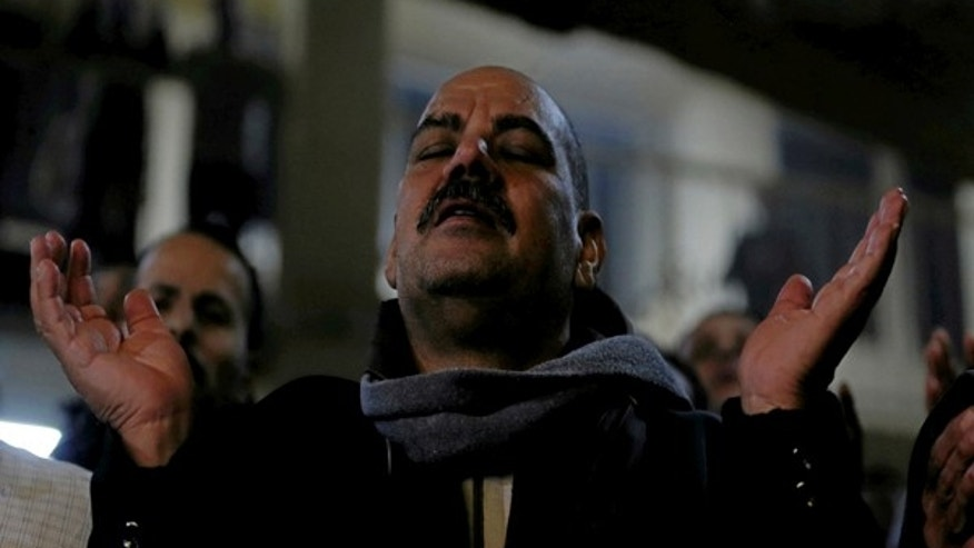 January 6, 2017: An Egyptian Christian attends Egypt's Coptic Christmas eve mass in a church of the Samaan el-Kharaz Monastery in the Mokattam Mountain area of Cairo, Egypt.