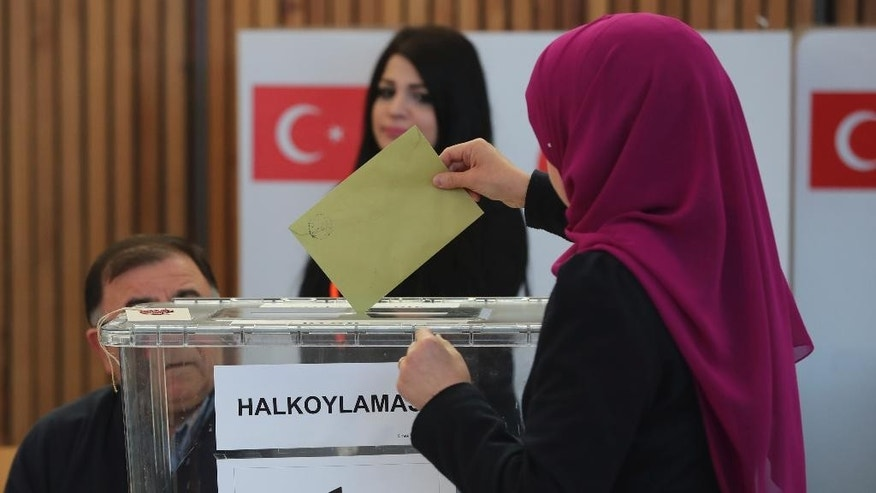 A woman casts her ballot in the referendum on a presidential system in Turkey in Fuerth, southern Germany, Monday, March 27, 2017. (Daniel Karmann/dpa via AP)