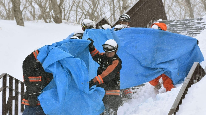 Rescuers carry the people who got injured in an avalanche at a ski resort in Nasu, Tochigi prefecture, Monday, March 27, 2017.