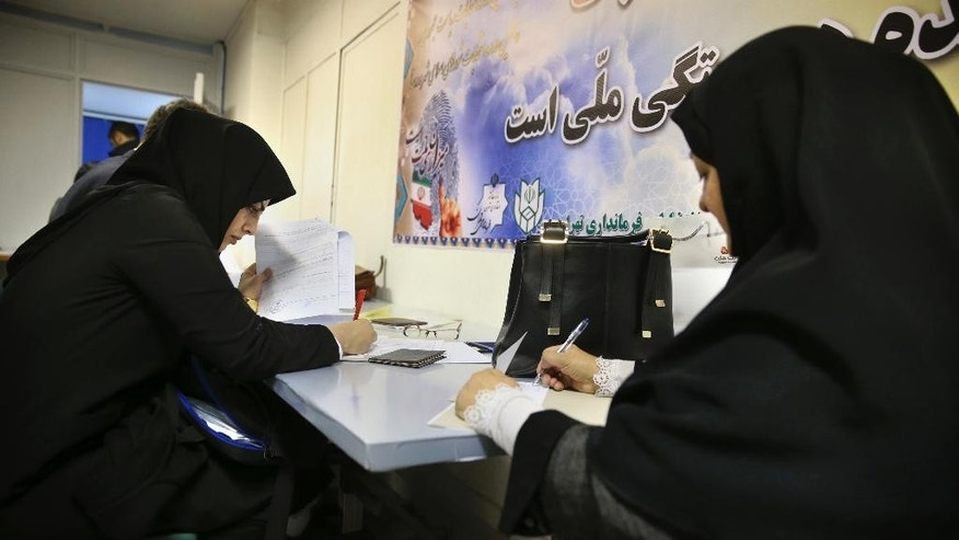 In this Sunday, March 26, 2017 photo, hopeful candidates for municipal elections, fill out official documents to register on the last day of registration, at the governorate building, in Tehran, Iran. Iran's state TV is reporting that a significantly higher number of Iranians have registered seeking to run in the municipal elections next month. The TV says 287,000 -- or 14 percent more than four years ago -- have submitted their candidacies, hoping to be approved to contest the vote for the nearly 110,000 council members for city councils across Iran. (AP Photo/Vahid Salemi)