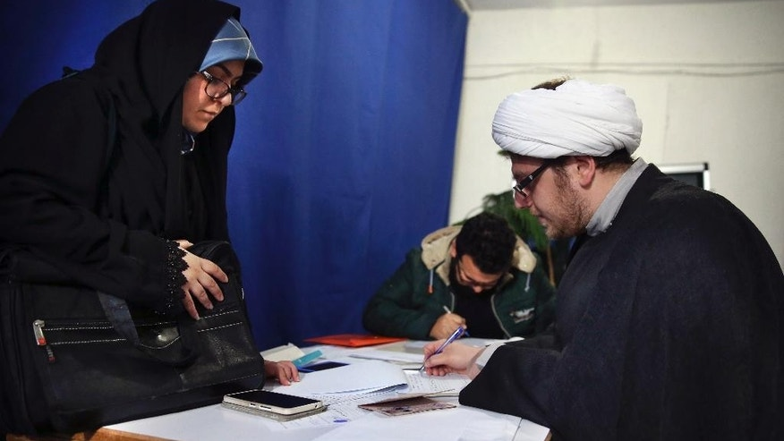 In this Sunday, March 26, 2017 photo, an Iranian clergyman fills out official documents to register on the last day of registration for municipal elections, at the governorate building, in Tehran, Iran. Iran's state TV is reporting that a significantly higher number of Iranians have registered seeking to run in the municipal elections next month. The TV says 287,000 -- or 14 percent more than four years ago -- have submitted their candidacies, hoping to be approved to contest the vote for the nearly 110,000 council members for city councils across Iran. (AP Photo/Vahid Salemi)