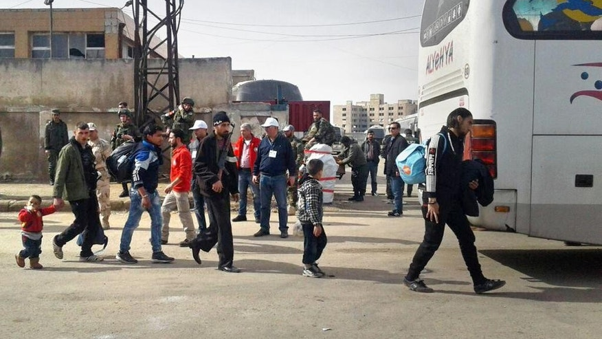 In this photo released by the Syrian official news agency SANA, a Syrian opposition gunman, center left, carries his weapon as some family members leave the al-Waer neighborhood bound for a town on the Turkish border, in Homs, Syria, Monday, March 27, 2017. Syrian state TV said Monday that another group of rebels with their families are leaving the last opposition-held neighborhood in the central city of Homs under a Russia-brokered deal with the government. The opposition fighters agreed to leave and the evacuations first started on March 18, after years of siege and bombardment at the hands of pro-government forces. (SANA via AP)
