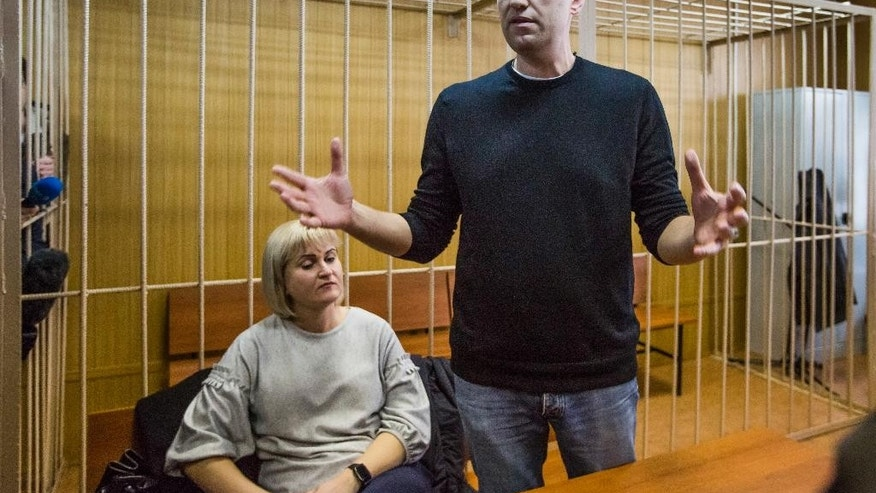 Russian opposition leader Alexei Navalny gestures while speaking, as his lawyer Olga Mikhailova listens, in court in Moscow, Russia, Monday, March 27, 2017. Navalny, who organized a wave of nationwide protests against government corruption that rattled authorities, was fined 20,000 rubles ($340) on Monday by a Moscow court. It was a comparatively lenient punishment for organizing an unsanctioned rally for which he faced up to 15 days in jail. The court has yet to deliver its ruling on charges accusing the opposition leader of resisting arrest. (AP Photo/Denis Tyrin)