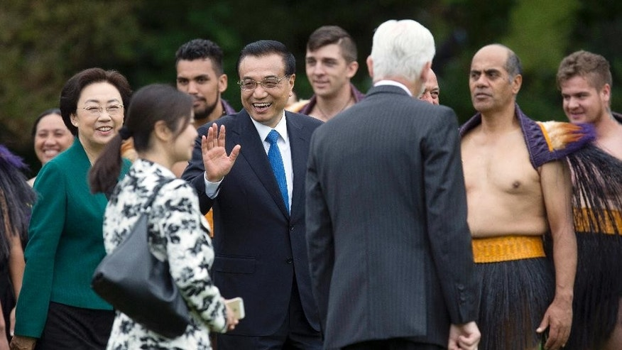 Chinese Premier Li Keqiang, center, walks with his wife Cheng Hong, left, as they arrive for an official welcoming ceremony at Government House in Wellington, New Zealand, Monday, March 27, 2017. Li is on three-day visit to New Zealand for high-level talks at a time that both countries are pushing to expand free trade. (Mark Mitchell/NZ Herald via AP)