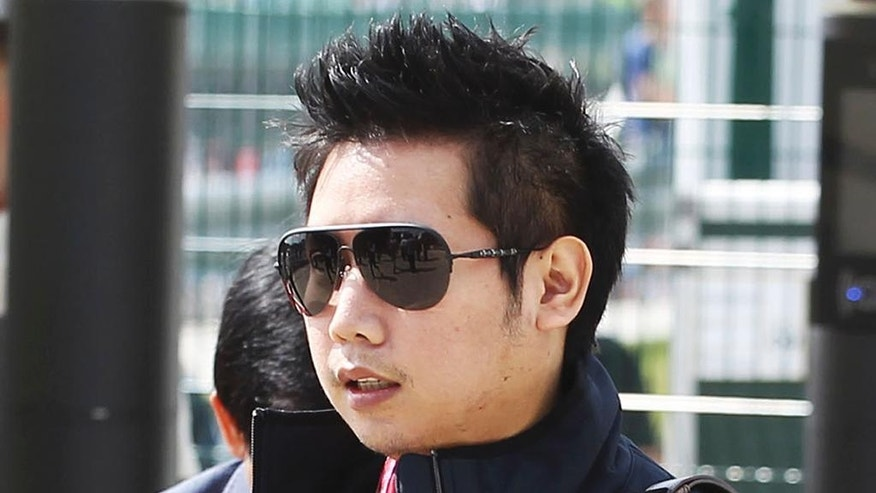 "In this June 30, 2013, photo provided by XPB Images, Vorayuth ""Boss"" Yoovidhya walks at the British Formula 1 Grand Prix in Silverstone, England. Vorayuth is accused of killing a Thai police officer in a hit-and-run in 2012, yet he still has not appeared to face charges. (XPB Images via AP)"