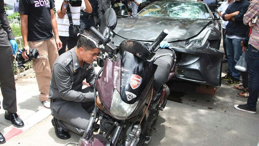 In this Sept. 3, 2012, photo, a Ferrari, that was driven by Vorayuth Yoovidhya, a grandson of late Red Bull founder Chaleo Yoovidhya, and a motorcycle, both involved in an accident, are displayed by police in Bangkok, Thailand. Vorayuth is accused of killing a Thai police officer in a hit-and-run in 2012, yet he still has not appeared to face charges. (Thai Daily News via AP)