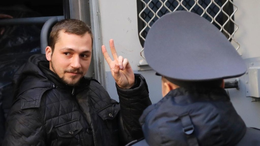An activist, detained at a rally, is escorted by police officers as he exits a police van for a court hearing in Minsk, Belarus, on Monday, March 27, 2017. About 400 people were arrested on Saturday in an unsanctioned protest against the authoritarian government of President Alexander Lukashenko, who has stifled dissent and independent media during his 23 years in power. (AP Photo/Sergei Grits)