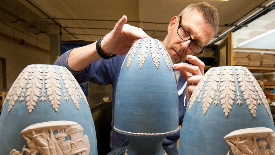 In this Monday, March 13, 2017 photo, a pottery worker puts final touches on ornamental vases at Wedgwood factory, in Stoke on Trent, England. Wedgwood has embarked on a sweeping revamp of its offerings to broaden its international market. Building on a heritage of making granny's china, Wedgwood is planning to capture the image of crumbling castles, Downton Abbey and Will & Kate as it expands to a younger audience and tries to tap into the zeitgeist of companies like Burberry _ except that they are doing it for homeware. (AP Photo/Rui Vieira)