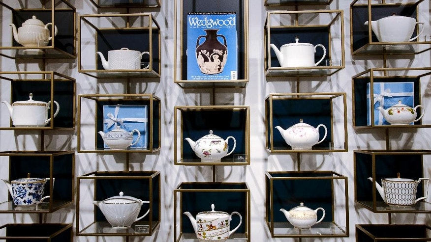 In this photo taken on Monday, March 13, 2017, classic British brand Wedgwood tea pots on display at Wedgwood visitor centre shop, in Stoke on Trent, England. Wedgwood has embarked on a sweeping revamp of its offerings to broaden its international market. Building on a heritage of making granny's china, Wedgwood is planning to capture the image of crumbling castles, Downton Abbey and Will & Kate as it expands to a younger audience and tries to tap into the zeitgeist of companies like Burberry _ except that they are doing it for homeware. (AP Photo/Rui Vieira)