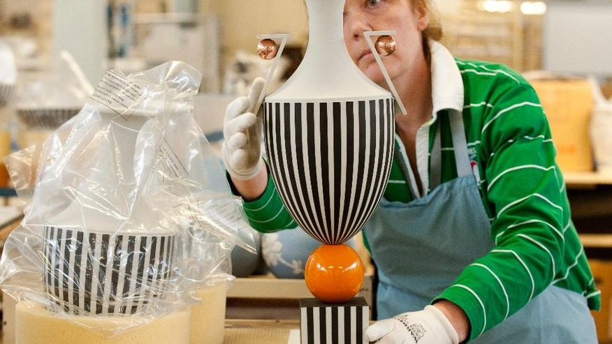 In this Monday, March 13, 2017 photo, a pottery worker puts the final touches to an ornament peace at Wedgwood factory, in Stoke on Trent, England, Monday March 13, 2017.  Wedgwood has embarked on a sweeping revamp of its offerings to broaden its international market. Building on a heritage of making granny's china, Wedgwood is planning to capture the image of crumbling castles, Downton Abbey and Will & Kate as it expands to a younger audience and tries to tap into the zeitgeist of companies like Burberry _ except that they are doing it for homeware. (AP Photo/Rui Vieira)