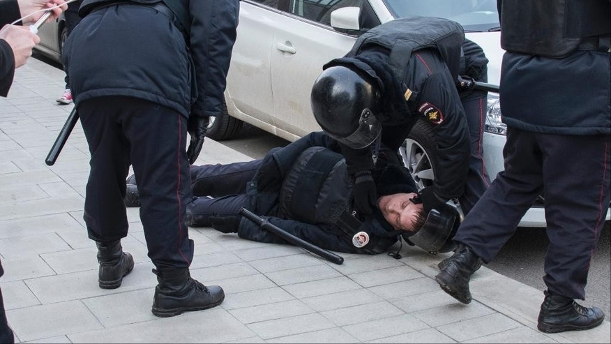 Police help a wounded comrade during fighting with protesters in Pushkin Square, downtown Moscow, Russia, Sunday, March 26, 2017. Thousands of people crowded into Moscow's Pushkin Square on Sunday for an unsanctioned protest against the Russian government, the biggest gathering in a wave of nationwide protests that were the most extensive show of defiance in years. (AP Photo/Artem Lunev)