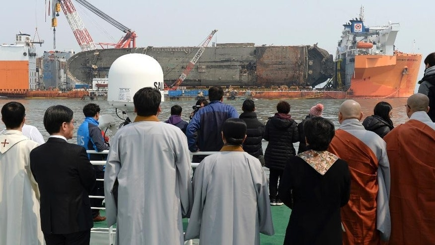 Relatives of the missing victims and clergymen attend religious services on a boat, near the sunken ferry Sewol on a semi-submersible transport vessel in waters off Jindo, South Korea, Tuesday, March 28, 2017. South Korea has held a memorial ceremony at sea for the nine passengers still missing from the 2014 ferry disaster that killed 304 passengers near the ship's wreckage that was raised from the waters last week. (Yonhap via AP)