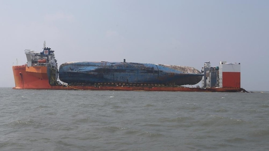 The sunken ferry Sewol is seen on the semi-submersible transport vessel during the salvage operation in waters off Jindo, South Korea, Monday, March 27, 2017. Salvage crews towed a corroded 6,800-ton South Korean ferry and loaded it onto a semi-submersible transport vessel Saturday, completing what was seen as the most difficult part of the massive effort to bring the ship back to shore nearly three years after it sank. (Seo Myung-gon/Yonhap via AP)