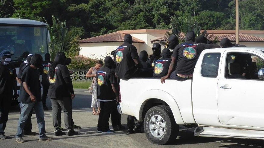 "Masked members of the collective ""500 Brothers"" are pictured at a roadblock outside the French Guiana capital, Cayenne, Monday, March 27, 2017. The Collective of 500 Brothers, the group largely behind the protests who have demanded that the French government send a minister to negotiate with them. French Guiana faced a nationwide strike Monday over crime and economic difficulties, amid protests that have paralyzed the French territory in South America, halted flights and a rocket launch and prompted a U.S. travel warning. (Deborah Neusy/France Guyane via AP)"