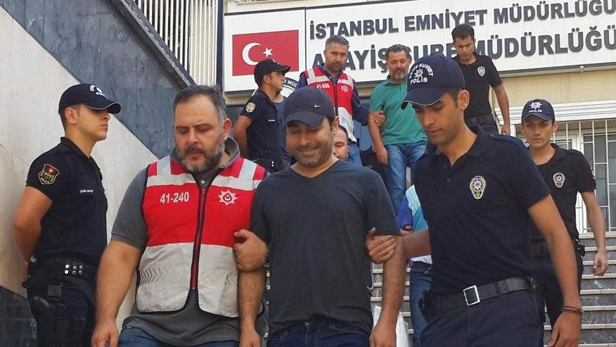 "In this Saturday, Sept. 3, 2016 photo, Turkish police officers escort Turkish pop singer Atilla Tas, centre, to the police headquarters following his arrest, in Istanbul. Tas and 28 other people, mostly journalists, went on trial Monday, March 27, 2017, on terrorism charges for alleged links to a failed coup attempt. They face up to 10 years in prison if convicted of membership in ""an armed terrorist organisation"" in a massive government crackdown that has included closing more than 100 media outlets and the arrests of reporters and editors suspected of ties to the July 15 insurrection. (DHA-Depo Photos via AP)"