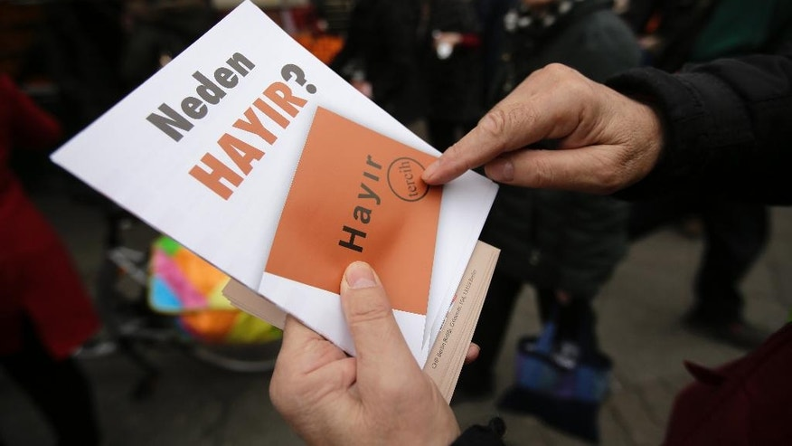 FILE - In this Tuesday, March 21, 2017 photo, a man hands out flyers, reading 'Why No' against the upcoming referendum in Turkey at the neighborhood Neukoelln in Berlin. Tensions are running high in Germany's Turkish immigrant community prior to a referendum in their old home country on expanding the Turkish president's powers. (AP Photo/Markus Schreiber)