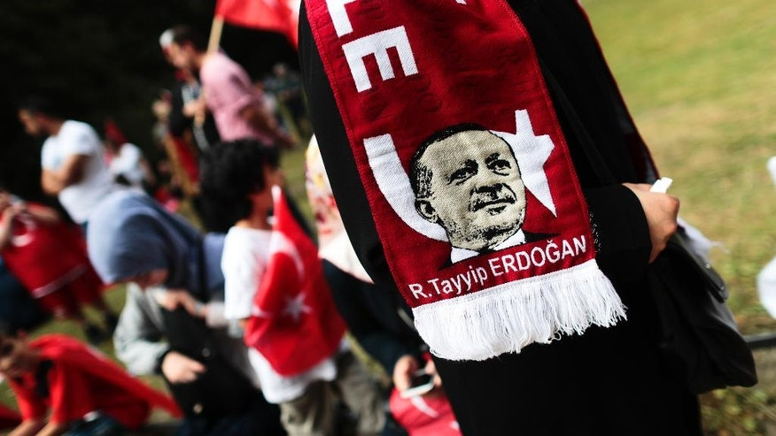 FILE - In this Saturday, July 16, 2016 file photo, a woman wears a scarf with a portrait of Turkish President Recep Tayyip Erdogan as she attends a demonstration against a coup attempt in Turkey, in front of the Turkish embassy in Berlin. Tensions are running high in Germany's Turkish immigrant community prior to a referendum in their old home country on expanding the Turkish president's powers. (AP Photo/Markus Schreiber)