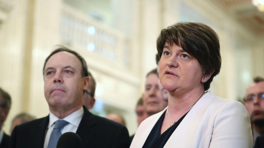 Democratic Unionist Party leader Arlene Foster, right, speaks to the media at Stormont in Belfast, flanked by Deputy DUP leader Nigel Dodds , left, as the deadline for restoring powersharing in Northern Ireland runs out later on Monday March 27, 2017. The British government faces a deadline on whether to extend negotiations on Northern Ireland's political future or renew direct control from London. Northern Ireland's latest unity government collapsed in January amid deepening disputes between the British Protestants of the Democratic Unionist Party and the Irish Catholics of Sinn Fein, (Niall Carson/PA Wire(/PA via AP)