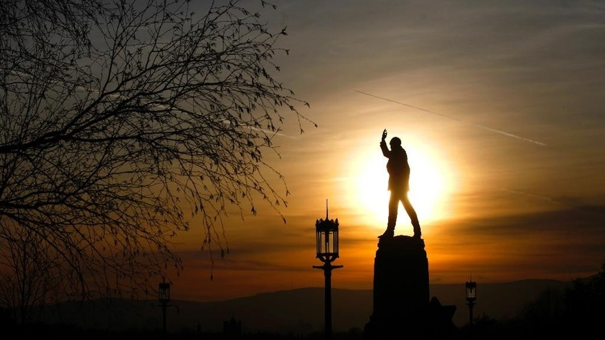 The sun sets behind the Edward Carson statue at Stormont in Belfast, Northern Ireland, Friday, March 24, 2017. Carson was a former Ulster Unionist Party leader between 1910-1920. Reminders of the past are everywhere in Belfast _ murals and memorials to those killed in the conflict, along with peace walls that separate predominantly Protestant neighborhoods from mostly Catholic ones _ but there are also new shopping malls and cafes, new tech industries, and lots of tourists. (AP Photo/Peter Morrison)