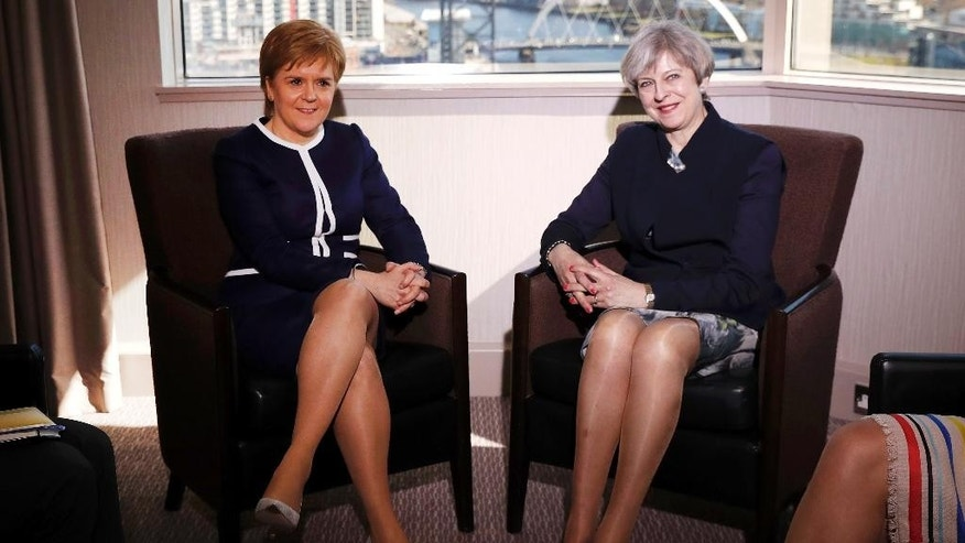 Britain's Prime Minister Theresa May, right,  and  Scotland's First Minister Nicola Sturgeon sit during their meeting in Glasgow, Scotland, Monday March 27, 2017. May met with Scotland's leader Monday for the first time since they faced off in a struggle over a new push for Scottish independence as the U.K. leaves the European Union. (Russell Cheyne/PA via AP)