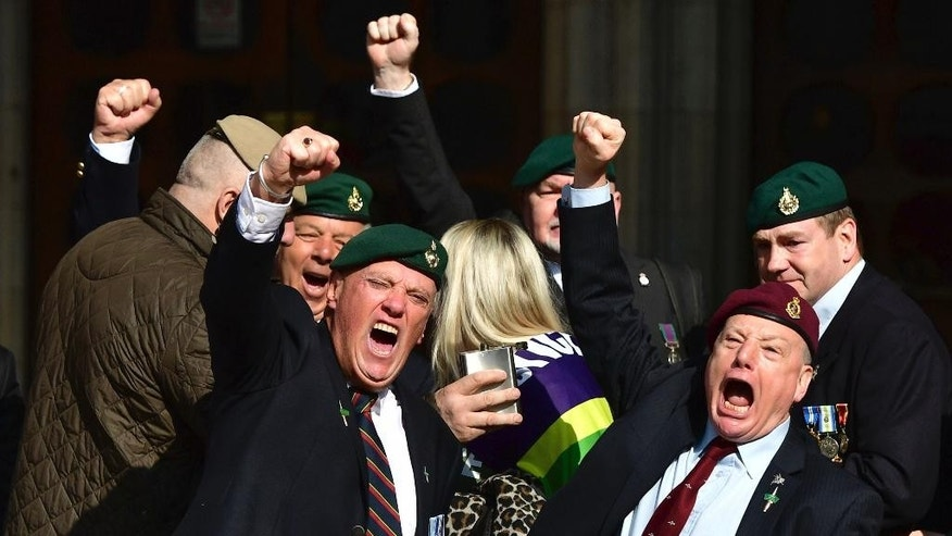 Supporters of Alexander Blackman celebrate outside the Royal Courts of Justice in London, Tuesday, March, 28, 2017. A British court has shortened the sentence of Royal Marine Blackman, convicted of killing a wounded Taliban fighter in Afghanistan. (Dominic Lipinski/PA via AP)