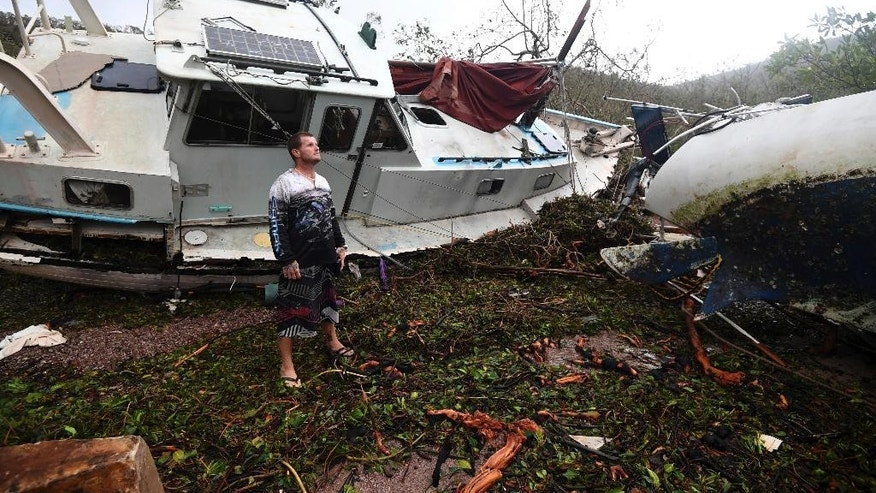 Bradley Mitchell inspects the damage to his uncle's boat after it smashed against the bank at Shute Harbour, Airlie Beach, Australia, Wednesday, March 29, 2017. Cyclone Debbie, which slammed into the coast of Queensland state on Tuesday with winds up to 260 kilometers (160 miles) an hour, weakened quickly as it moved inland and was downgraded to a tropical low by Wednesday morning. (Dan Peled/AAP Image via AP)