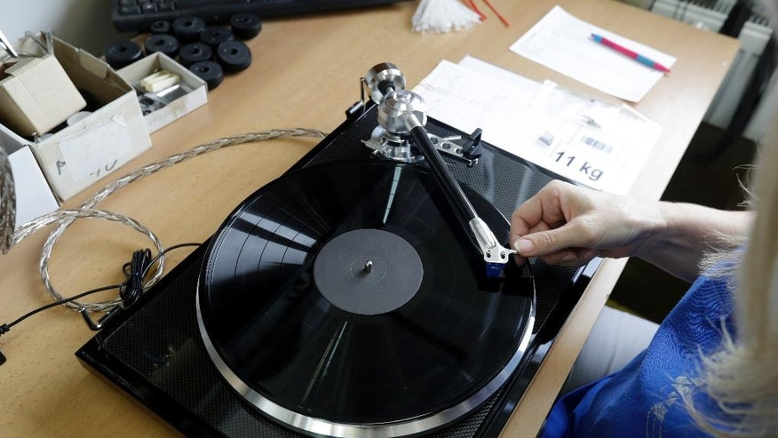 In this picture taken on Tuesday Feb. 28, 2017 in Litovel, Czech Republic, a worker checks a turntable at the SEV Litovel turntable factory. The company is considered the biggest maker of quality turntables in the world and has been increasing output year after year with the end of the market surge nowhere in sight. (AP Photo/Petr David Josek)