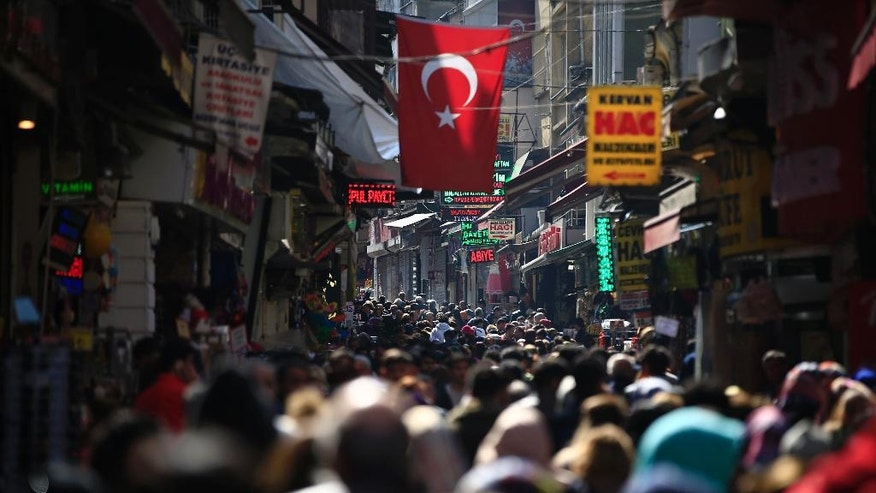 FILE  - In this Friday, March 24, 2017 file photo, people fill an open market in the historic Sultanahmet district of Istanbul. Times have been hard for Turkey, buffeted by bombings, violence between government forces and Kurdish rebels, refugee flows from the war in neighbouring Syria and a failed coup attempt that unleashed a huge crackdown under an ongoing state of emergency. On April 16, 2017, Turks will decide whether to make the post of president more powerful in a constitutional referendum that is a big gamble for tough-talking president Recep Tayyip Erdogan.(AP Photo/Lefteris Pitarakis, file)