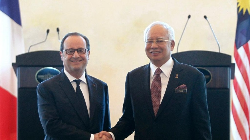 French President Francois Hollande, left,  and Malaysian Prime Minister Najib Razak shake hands after a press conference at Seri Perdana Building in Putrajaya, Malaysia on Tuesday, March 28, 2017. (AP Photo/Daniel Chan)
